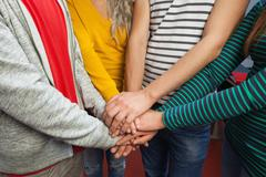 Close up of students holding hands together - stock photo