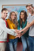 Cheerful casual students holding hands together - stock photo