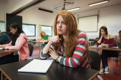 Bored female student listening in class Stock Photos