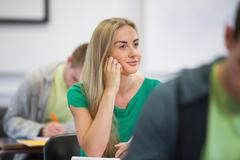 Happy blonde student listening in class Stock Photos