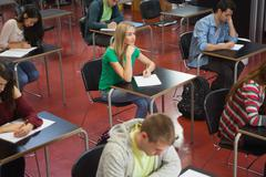 Stock Photo of Students taking notes in classroom with one blonde girl looking up from paper