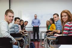 Students and lecturer smiling at camera in classroom - stock photo