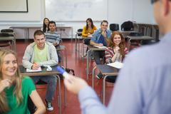 Students listening happily to their lecturer in class - stock photo