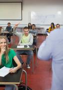 Student raising his hand to ask a question in classroom - stock photo