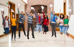 Happy students jumping for joy holding exam results in a hallway Stock Photos