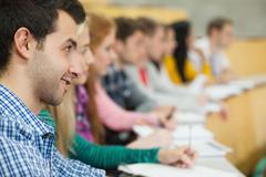 Row of smiling students listening in a lecture hall Stock Photos