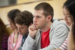 Row of concentrating students taking notes in a lecture hall - stock photo