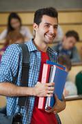 Stock Photo of Happy student standing in front of his class in lecture hall