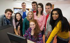 Happy students standing at computer in the computer room - stock photo