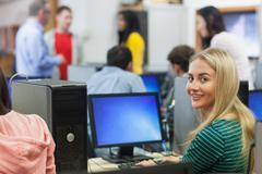 Blonde student smiling at camera in computer room - stock photo