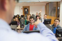 Smiling students listening to lecturer in their computer class - stock photo