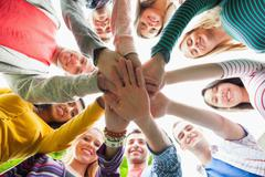 Group of smiling students putting hands in a circle on campus Stock Photos