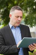 Focused lecturer using his tablet outside on campus Stock Photos