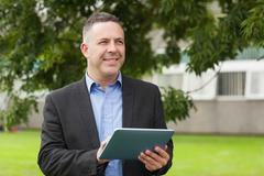 Stock Photo of Smiling lecturer using his tablet pc outside on campus