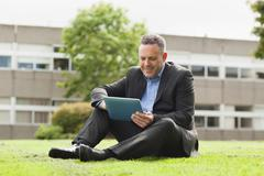 Smiling lecturer using his tablet pc sitting outside on campus - stock photo