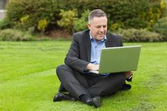 Stock Photo of Smiling lecturer sitting outside on campus using his laptop