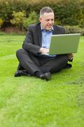 Happy lecturer sitting outside on campus using his laptop - stock photo