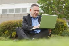 Stock Photo of Smiling professor sitting outside on campus using his laptop