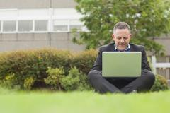 Happy professor sitting outside on campus using his laptop - stock photo