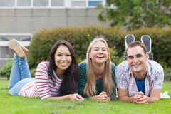 Stock Photo of Happy young students smiling at camera outside on campus