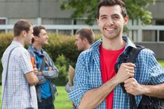 Stock Photo of Happy student smiling at camera in front of his classmates