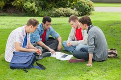 Students studying together outside on campus - stock photo
