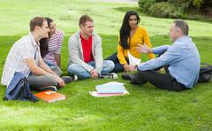 Stock Photo of Happy students chatting with lecturer sitting outside on campus