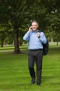 Professor walking across campus talking on the phone Stock Photos