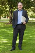 Stock Photo of Smiling professor standing on campus holding notepads