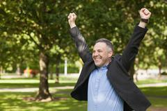 Excited lecturer cheering outside on campus - stock photo