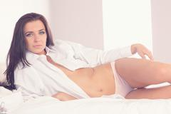 Gorgeous brunette woman wearing a white shirt lying on her bed - stock photo