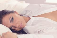 Stock Photo of Lovely calm woman lying on her bed wearing a white shirt