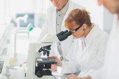 Woman standing looking through microscope Stock Photos