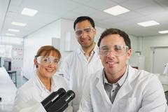 Ryhmä tiedemiehiä poseeraa laboratoriossa Kuvituskuvat