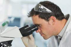 Handsome young scientist looking through a microscope - stock photo