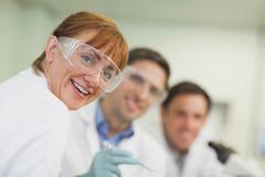 Amused nainen tiedemies seisoo laboratoriossa kollegoidensa kanssa Kuvituskuvat