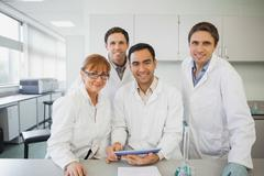 Some scientists standing behind a desk in the laboratory holding a tablet Stock Photos
