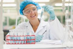 Smiling student holding test tube containing liquid Stock Photos