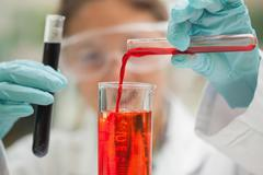 Student pouring red liquid beaker Stock Photos