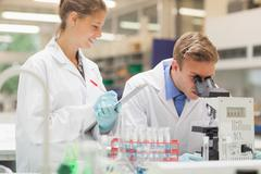 Stock Photo of Two students looking through microscope and taking notes