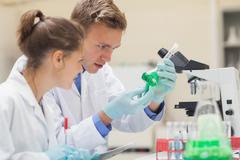 Two focused students looking through microscope and taking notes - stock photo