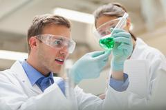 Stock Photo of Two students looking at green liquid and taking notes