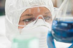Lab assistant with mask looking closely at blue liquid - stock photo