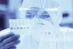 Lab assistant with mask looking closely at test results - stock photo