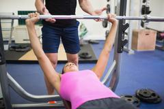 Stock Photo of Trainer helping lying sporty woman exercising with barbell
