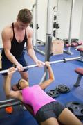 Stock Photo of Strong trainer helping lying woman exercising with barbell