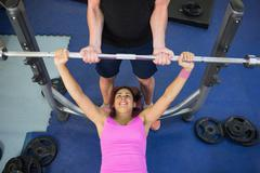 Stock Photo of Instructor helping lying happy woman exercising with barbell