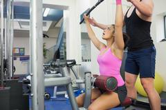 Instructor assisting brunette at weight machine - stock photo