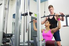 Stock Photo of Instructor assisting fit brunette at weight machine