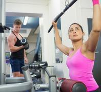 Stock Photo of Serious brunette training at weight machine